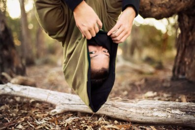 Portrait of woman in hooded jacket hanging upside down from tree