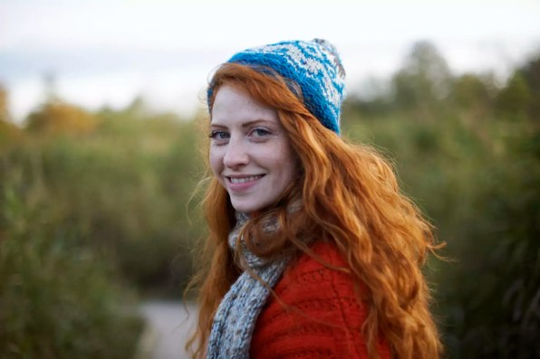 Portrait of red haired woman looking over shoulder at camera smiling