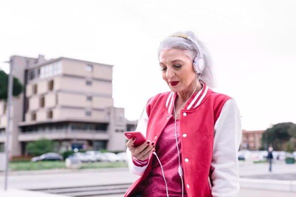 Mature woman in baseball jacket listening to headphones and looking at smartphone