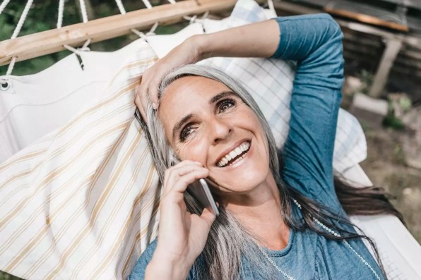 Portrait of laughing woman on the phone lying in hammock