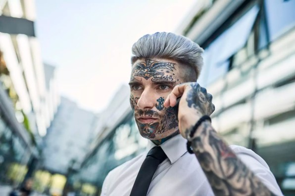 Young businessman with tattooed face, talking on he phone
