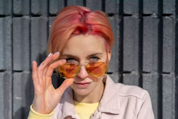 Portrait of young woman, sun glasses and pink jeans jacket