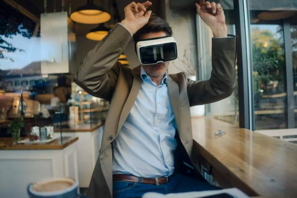 Mature businessman sitting in coffee shop, looking through VR glasses, dancing