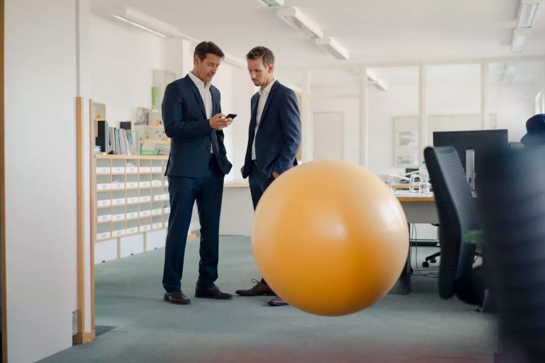 Two businessman checking smartphone with yellow fitness ball in foreground