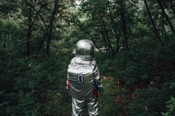 Spaceman exploring nature, walking in forest