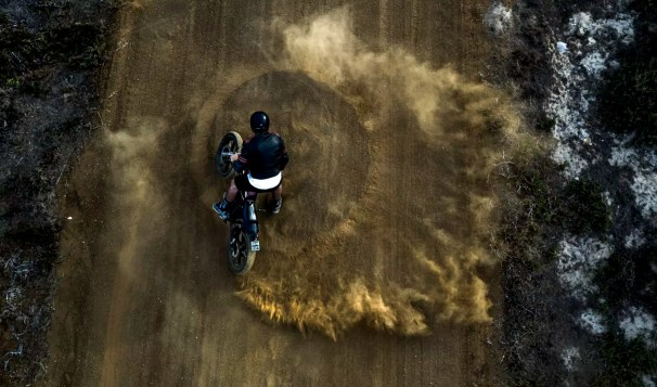 High angle view of man driving cafe racer motorcycle in circles on a dusty dirt road.