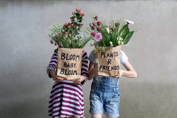 Two girls standing side by side hiding behind paper bags with flowers