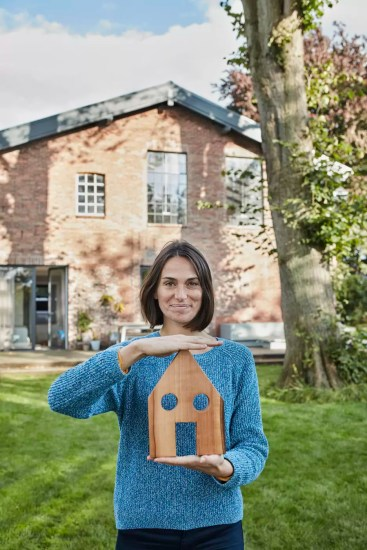 Portrait of smiling woman in garden of her home holding house model