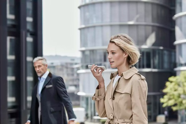 Germany, Duesseldorf, portrait of blond businesswoman wearing beige trenchcoat talking on mobile phone
