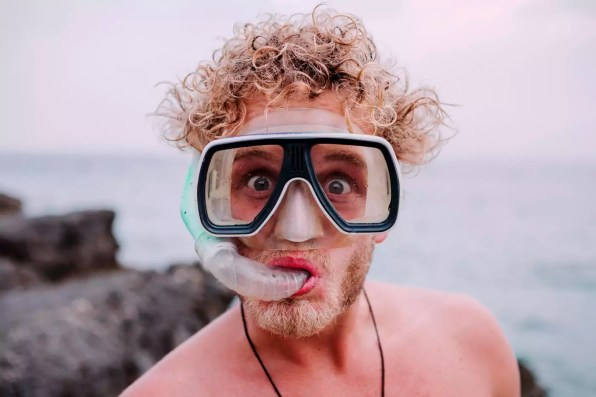Portrait of young man with diving goggles and snorkel pulling funny faces