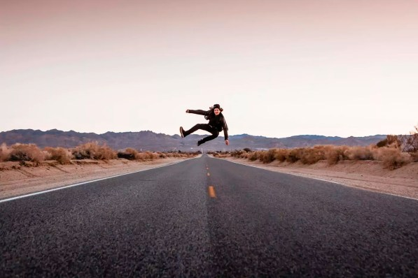 USA, California, Joshua Tree, young man jumping on a road