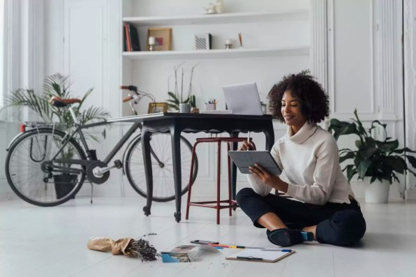 Disigner sitting on ground of her home office, using digital tablet
