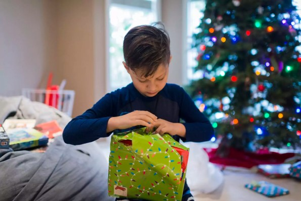 Boy wrapping Christmas present while sitting at home