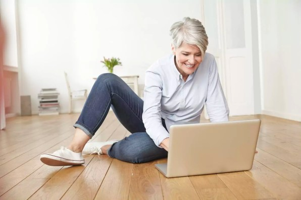 Mature woman sitting on floor using laptop