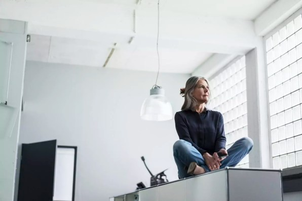 Senior woman sitting on a cabinet in office