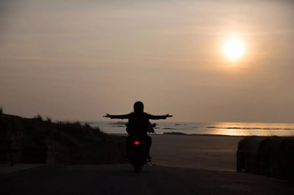Silhouette of young couple on motorcycle at sunset