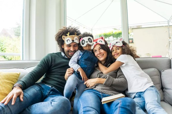 Happy family sitting on couch, wearing animal masks