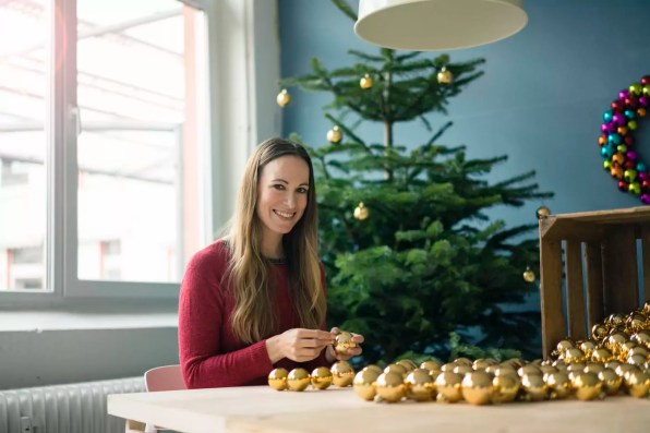 Portrait of smiling woman sitting at table with many golden Christmas baubles