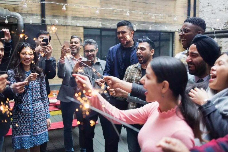 Friends enjoying party, celebrating with sparklers