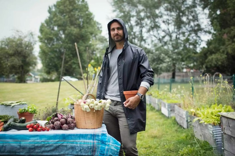 Portrait of mid adult man standing by freshly harvested vegetables on table at urban garden