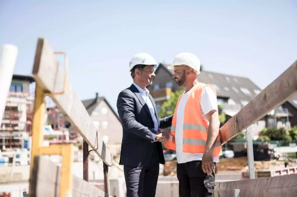 Man in suit shaking hands with construction worker on construction site