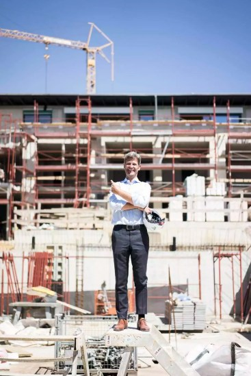 Portrait of happy man standing on construction site