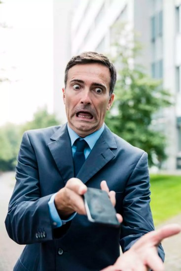 Shocked businessman with cell phone in the city