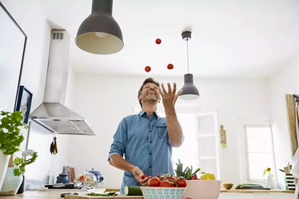 Mature man standing in kitchen, juggling with tomatoes
