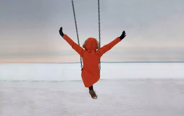 Rear view of woman with arms outstretched swinging over snow covered landscape against cloudy sky