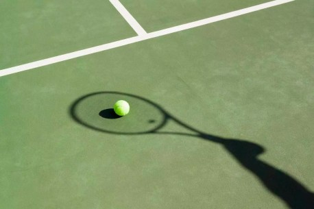 Shadow of a tennis racquet on a tennis court