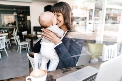 Businesswoman in cafe holding baby