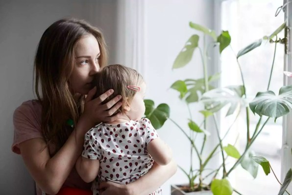 Mother kissing daughter while looking through window at home