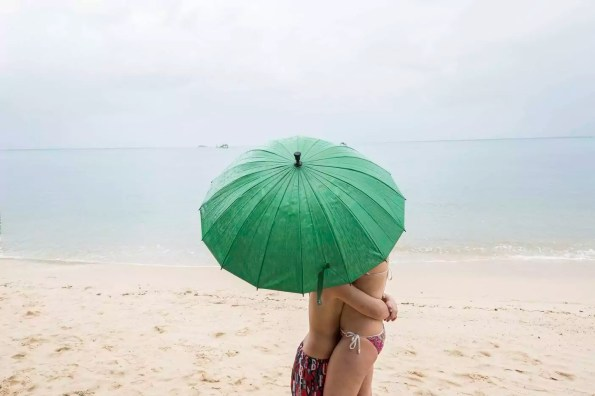 Thailand, boy hugging his mother on the beach under a green umbrella