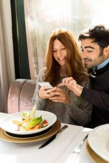 Happy couple using cell phone in a restaurant