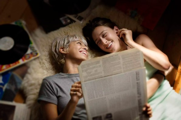Overhead view of happy woman holding vinyl record while lying with friend on floor