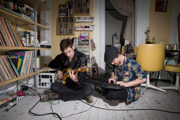 Two young men playing instruments in their living room