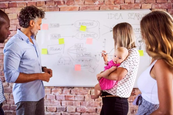 Mother with baby working together with team on whiteboard at brick wall in office