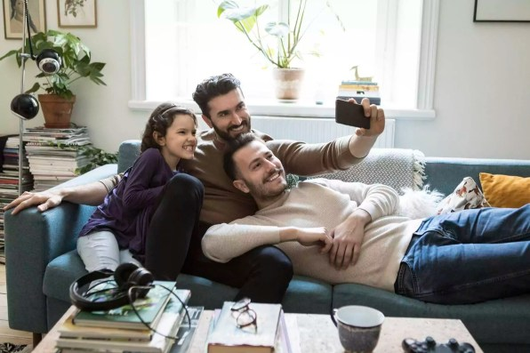 Fathers taking selfie with daughter through mobile phone on sofa at home