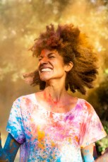 Woman shaking her head, full of colorful powder paint, celebrating Holi, Festival of Colors