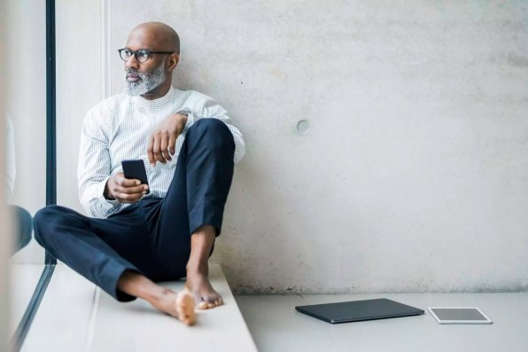 Barefoot mature businessman with smartphone sitting on window sill looking at distance