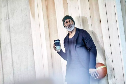 Mature businessman with takeaway coffee and basketball at wooden wall