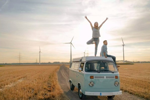 Young couple on roof of a camper van in rural landscape
