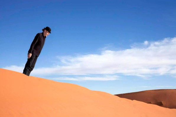 Morocco, Merzouga, Erg Chebbi, man wearing a bowler hat standing crooked on desert dune