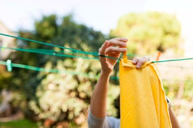 Close-up of woman hanging up yellow blanket on clothesline