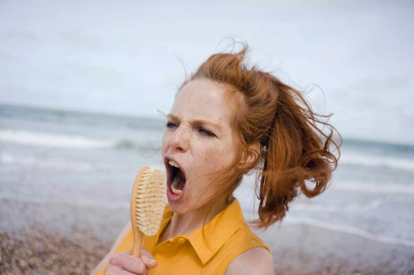 Woman using hair brush at the sea as a microphone
