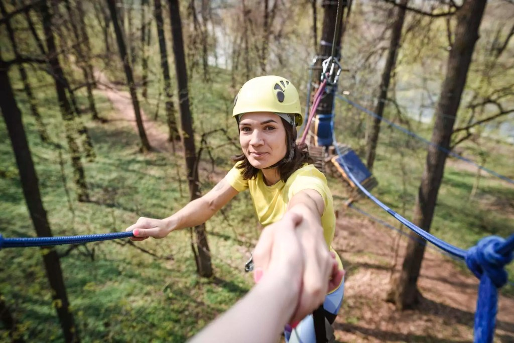 young smiling woman giving her hand in a rope course - EYAF00205