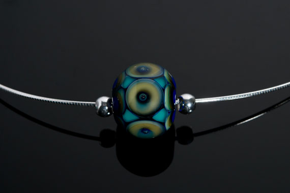 """Becky Congdon """"Peacock Eyes Omega"""" handmade flameworked glass bead with sterling silver findings/chain 18"""" $95. Inquire on availability(photo by Ann Cady)"""