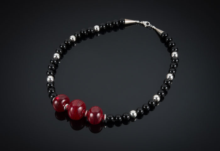 "Becky Congdon ""Snap, Crackle, Pop! Necklace"" 21.5"" handmade flameworked glass hollow red beads with sterling silver and onyx gemstone beads $225. SOLD (photo by Ann Cady)"
