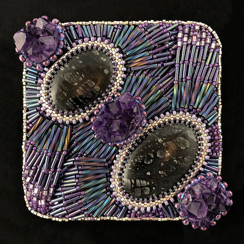 "San Fortune ""Line the Nest"" 3.5x3.5 bead embroidery on framed black panel 3 amethyst crystals, 2 black jasper stones w/ beaded seed bead bezels, layers of glass bugle and seed beads $290."