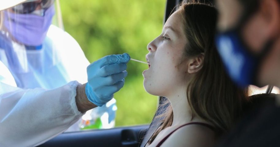 A health care worker gives a girl a throat swab test at a drive-in coronavirus testing center in Los Angeles.
